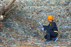 Workers in landfill dumping, Check the plastic bottles in the recycling plant.  royalty free stock photos