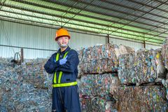 Workers in landfill dumping, Garbage engineer, recycling, wearing a safety suit standing in the recycling center have a plastic. Bottle for recycling in the royalty free stock image