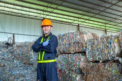 Workers in landfill dumping, Garbage engineer, recycling, wearing a safety suit standing in the recycling center have a plastic. Bottle for recycling in the royalty free stock photography