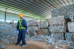 Workers in landfill dumping, Garbage engineer, recycling, wearing a safety suit standing in the recycling center have a plastic. Bottle for recycling in the stock images