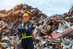Workers in landfill dumping, Garbage engineer, recycling, wearing a safety suit standing in the outdoor recycling center have a. Metal scrap pile in the royalty free stock photography