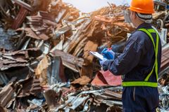 Workers in landfill dumping, Garbage engineer, recycling, wearing a safety suit standing to check the amount of recycled metal. Scrap stock photography