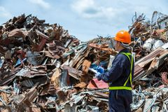 Workers in landfill dumping, Garbage engineer, recycling, wearing a safety suit standing to check the amount of recycled metal. Scrap royalty free stock images