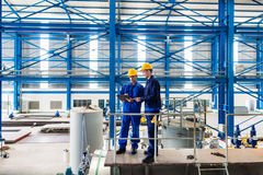 Workers in large metal workshop checking work. Two workers in large metal workshop or factory checking work standing on large machine Royalty Free Stock Photo