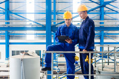 Workers in large metal workshop checking work Royalty Free Stock Photo
