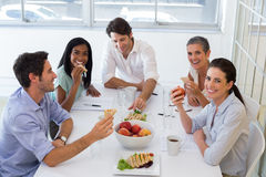 Workers laugh while eating sandwiches for lunch Royalty Free Stock Images