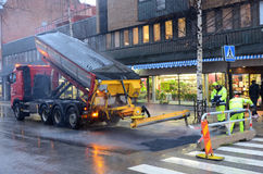 Workers Laying Asphalt. In the rainy weather conditions Royalty Free Stock Images