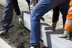 Workers laying breeze blocks. Closeup of workers laying breeze blocks outdoors on building site royalty free stock image