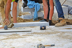 Workers laying granite block paver in place. Permeable paving installation series Royalty Free Stock Image