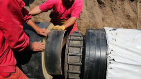 Workers Laying Heavy Underground Pipes. New pipes for the reconstruction of city heating system Royalty Free Stock Photo