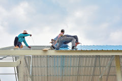 Workers are laying roof on steel frame. royalty free stock photography