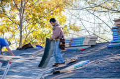 Workers laying shingles on a roof Royalty Free Stock Photos