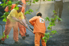 Workers leveling hot asphalt Royalty Free Stock Photos