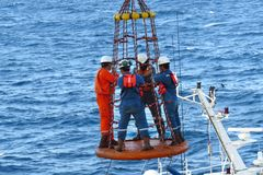 Workers are lifted by the crane to the offshore platform. Transfer crews by personal basket from the platform to crews boat royalty free stock photography