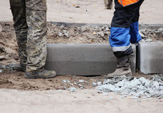 Workers are lifting concrete curb. Concrete kerb installation at sidewalk edging. Sidewalk replacement Stock Images