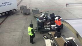 Workers are loading luggage in passenger airplane in the airport of Arkhangelsk. stock video footage