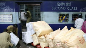 Workers loading packages into train at train station in Mumbai. stock footage