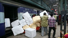 Workers loading packages into train at train station in Mumbai. stock video
