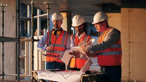 Workers look at a blueprint on a building site.