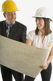 Workers looking at blueprints of jobsite Royalty Free Stock Photo