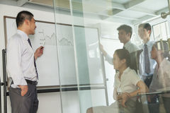 Workers looking on the diagram on the whiteboard Stock Photo