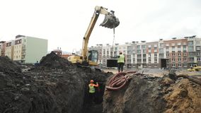 Workers lowering concrete manhole ring of excavator ladle down the ditch stock video