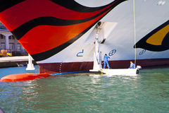 Workers make maintenance service at the anchor of a cruise passe. TRIESTE, ITALY - OCTOBER 26, 2014 Two workers clean and make maintenance service to the anchor Royalty Free Stock Photography