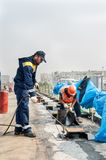 Workers make waterproofing of seams on the bridge Royalty Free Stock Image