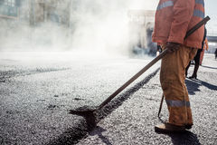 Workers making asphalt with shovels at road Stock Photography
