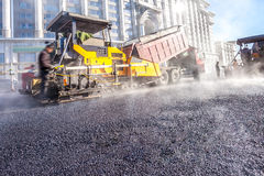 Workers making asphalt with shovels at road constructio Stock Photo