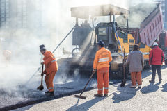 Workers making asphalt with shovels at road constructio Royalty Free Stock Images