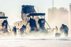 Workers making asphalt with shovels at road constructio Royalty Free Stock Photo