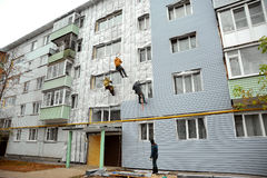 Workers making repairs on a facade of a building Royalty Free Stock Photo