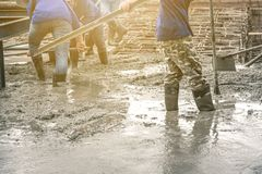 Workers man using a Vibration Machine for eliminate bubbles in concrete. After Pouring ready-mixed concrete on steel reinforcement to make the road by mixing stock image