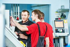 Workers at manufacture workshop. Three industrial workers at cnc turning machine center in tool manufacture workshop Royalty Free Stock Image