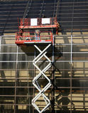 Workers on mechanical lift. Repairing office windows Royalty Free Stock Image