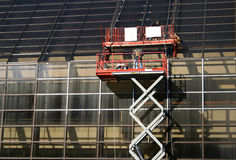 Workers on mechanical lift. Repairing office windows Royalty Free Stock Photography