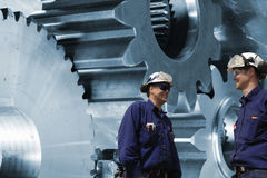 Workers, mechanics with cogwheels and gears Royalty Free Stock Photography