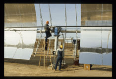 Workers in Mojave Desert Build Solar Thermal Power plant. Workers in the California Mojave Desert Build Solar Thermal Power plant using parabolic curved mirrors Stock Photography
