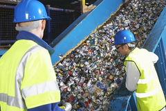 Workers Monitoring Conveyor Belt Of Recycled Cans