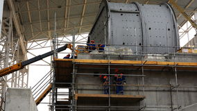 Workers mount a grinding mill for ores of ferrous and non-ferrous metals at a concentrating mill