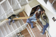 Workers move the safe on a lstaircase Stock Photo