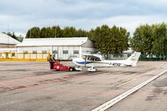 Workers moving Cessna 172 SP airplane to hangar. Stock Photo