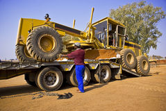 Workers Moving a Grader - Caterpillar 140H Transpo royalty free stock image