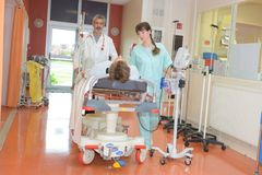 Workers moving patients in hospital. Translating stock image