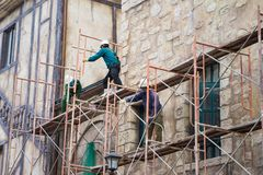 Workers with no protection belt fixed on scaffold at construction site Royalty Free Stock Photo