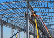 Free Workers On Aerial Work Platforms Build The Metal Structure Of The Roof Of A Large Building. Stock Image - 175795401