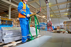 Workers operates crane-beam in manufacturing workshop Stock Image