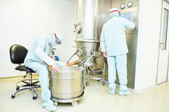 Workers operating pharma fluid bed system Stock Photography