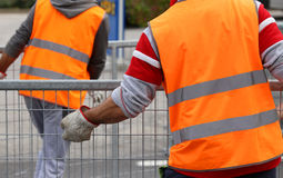 Workers with orange high-visibility vest while moving the iron f Stock Images